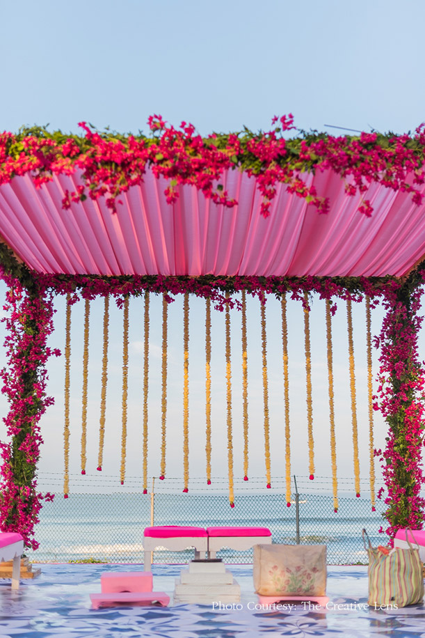 Mandap made out of Pink flowers and green foliage, pink seating and yellow flowers